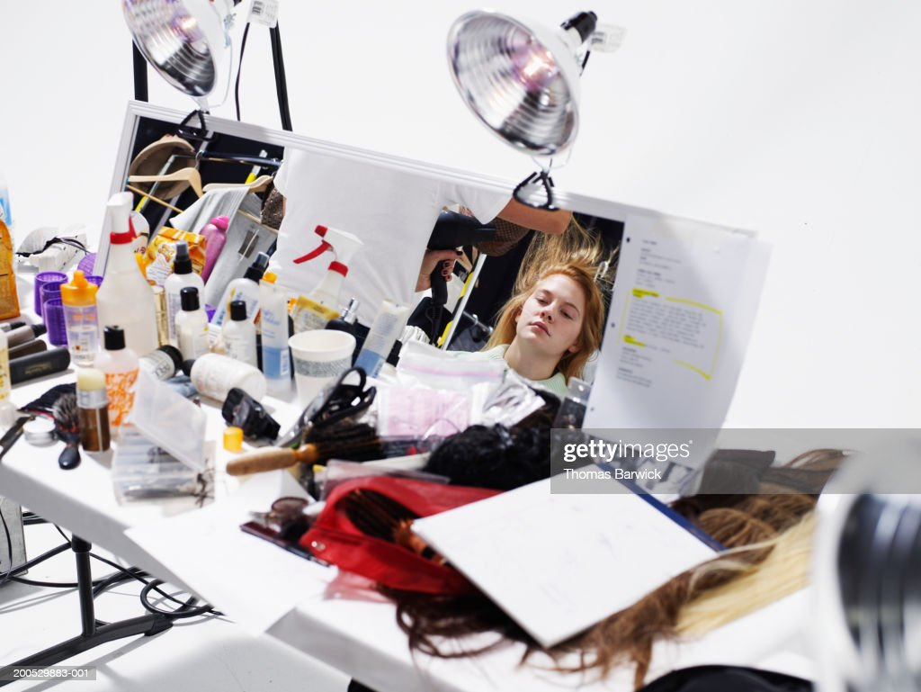 Young female model having hair styled (focus on reflection in mirror) : Stock Photo