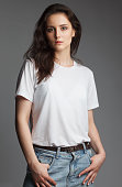 attractive female model four thirds view in blank white t-shirt and jeans isolated on gray background