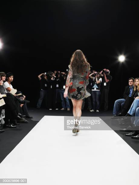 Young female model on catwalk, group of photographers in background