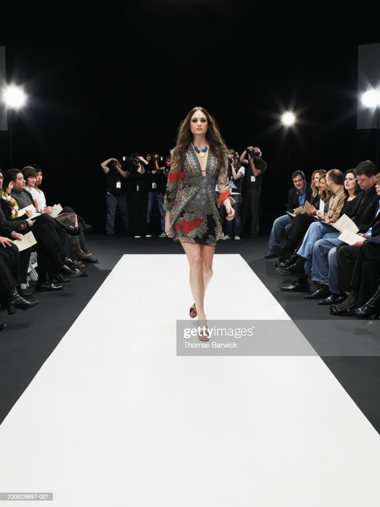 Young female model on catwalk, group of photographers in background : Stock Photo