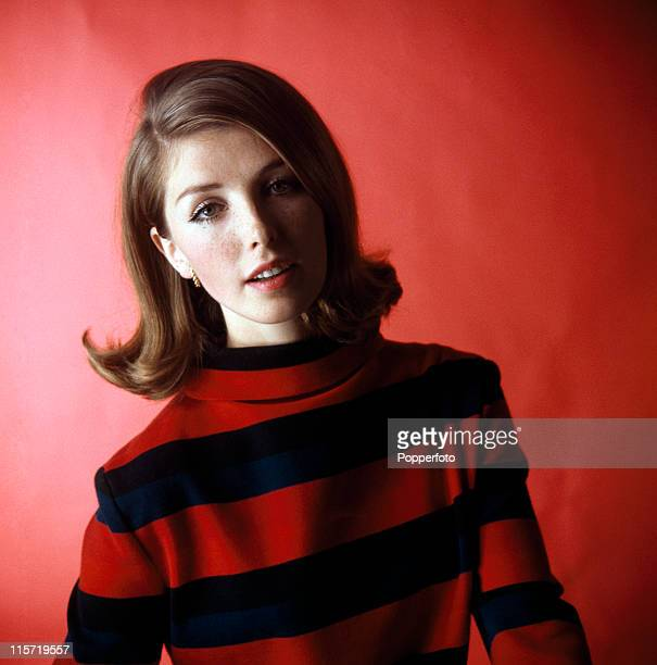 A young female model with brown mediumlength hair wearing a cowlneck navy blue and red striped knitted top in a studio setting circa 1965
