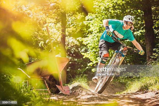Young female mountain biker riding forest track