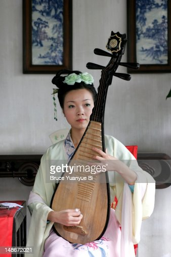 Young female musician in traditional dress playing Pipa, traditional plucked string instrument, inside hall of Zhouzheng Yuan (Humble Administrator's Garden).