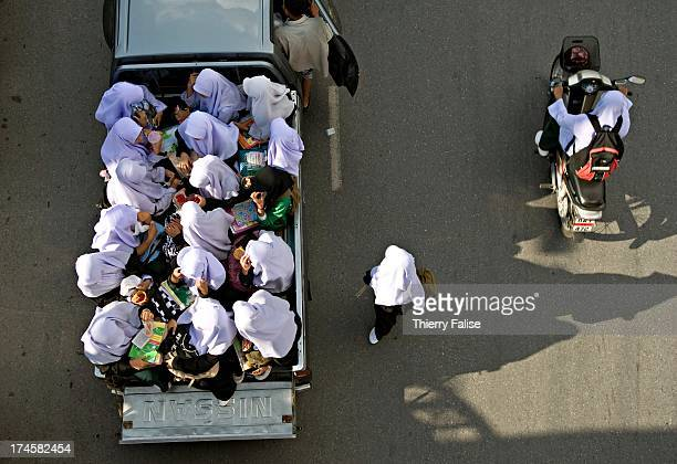 Young female Muslim students are huddling together in a pickup truck after a school day on a main road of Yala one of the three southernmost Thailand...