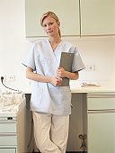 Young female nurse holding clipboard in kitchen, portrait