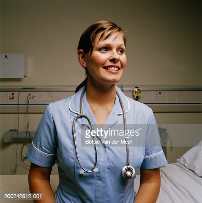 Young female nurse, smiling, close-up : Stock Photo