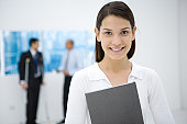 Young female office worker holding file, smiling at camera
