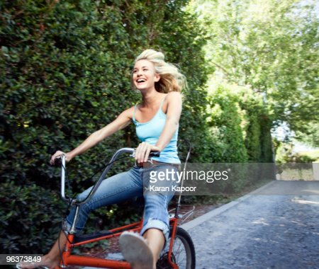 Young female on copper cycle : Stock Photo