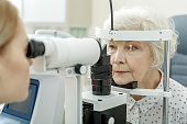 Oculist is sitting afore patient and checking her sight with help of optical equipment