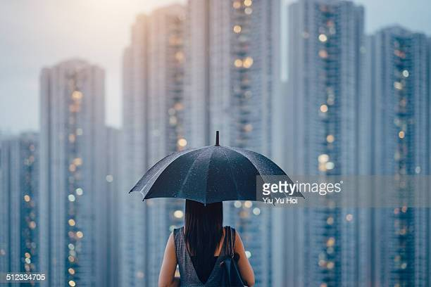 Young female overlooking cityscape on a rainy day