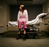 Young female patient sitting on edge of hospital bed