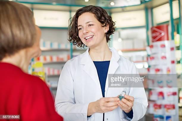 Jeune femelle pharmacien aider le client