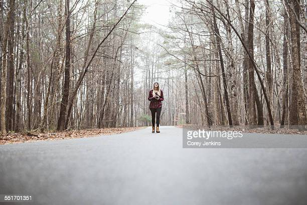Young female photographer standing on rural forest road