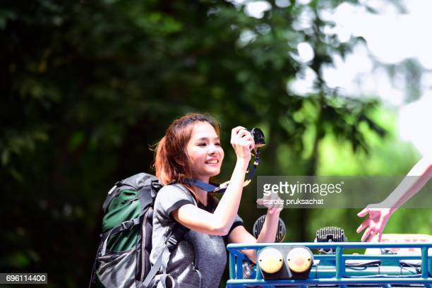 Young female photographer taking photos on traveled car and background  nature .