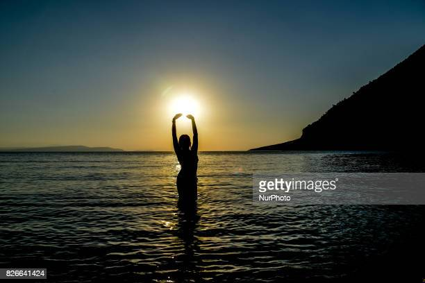 A young female playing in the water standing in contrast to the sunset at Dafni Messopion Euboea on August 4 2017
