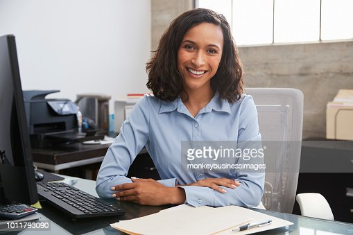 Young female professional at desk smiling to camera : Foto stock