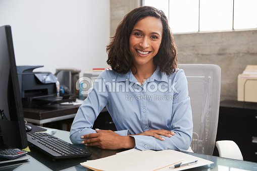Young female professional at desk smiling to camera : Stock Photo