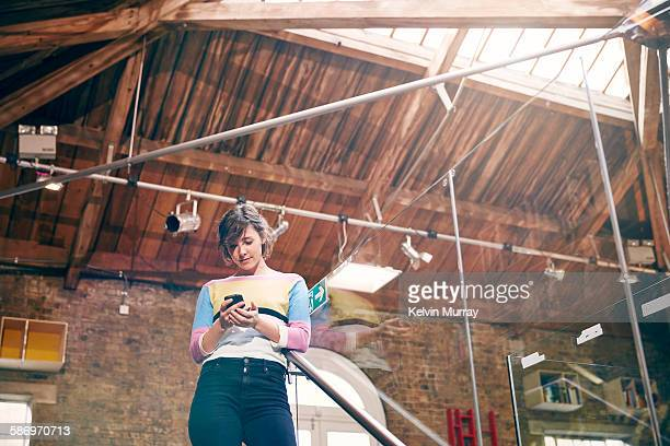 A young female professional checks her smartphone