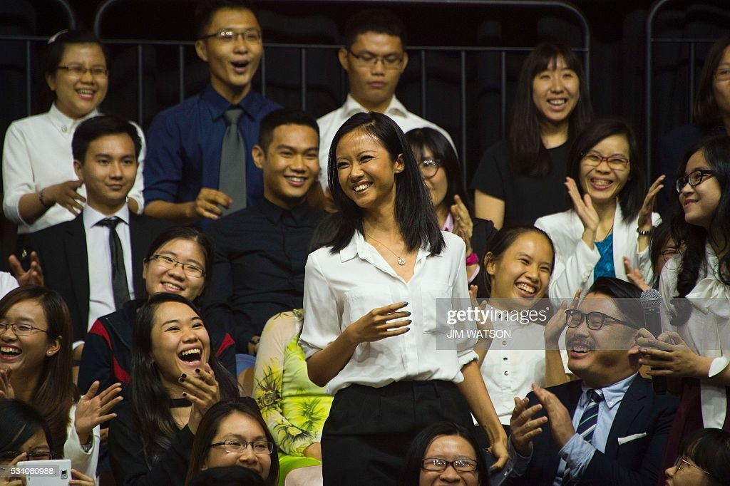 A young female rapper smiles after singing a verse to her song while asking US President Barack Obama a question at the Young Southeast Asian Leaders Initiative town hall event in Ho Chi Minh City on May 25, 2016. Obama urged communist Vietnam on May 24 to abandon authoritarianism, saying basic human rights would not jeopardise its stability, after Hanoi barred several dissidents from meeting the US leader. / AFP / JIM
