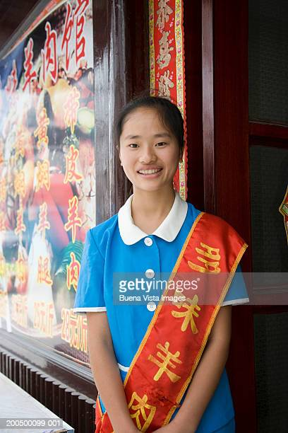 Young female receptionist by restaurant, smiling, portrait