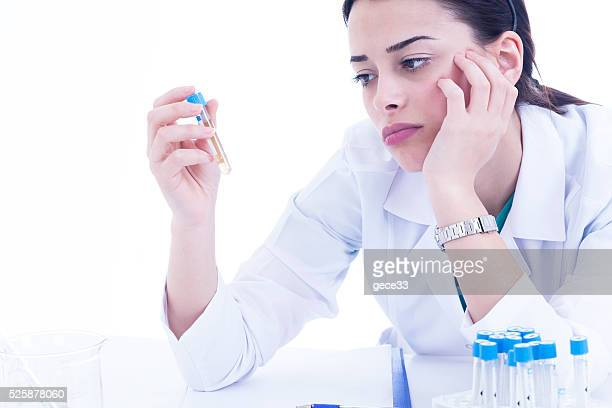 Young female researcher bored on white background