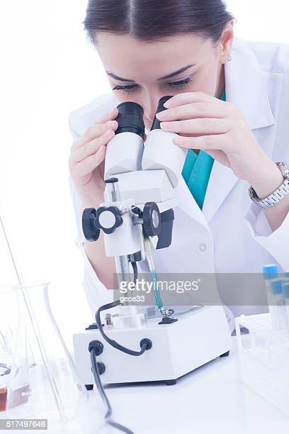 Young female researcher using microscope on white background