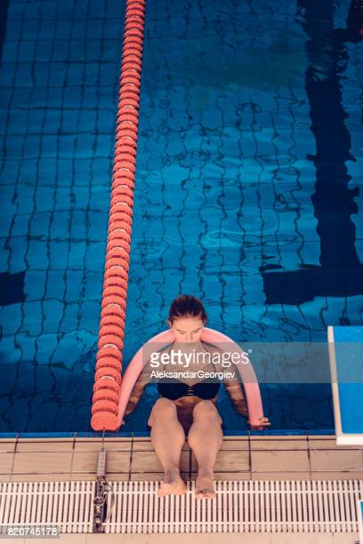Young Female Resting After Water Aerobics Class at Indoor Swimming Pool