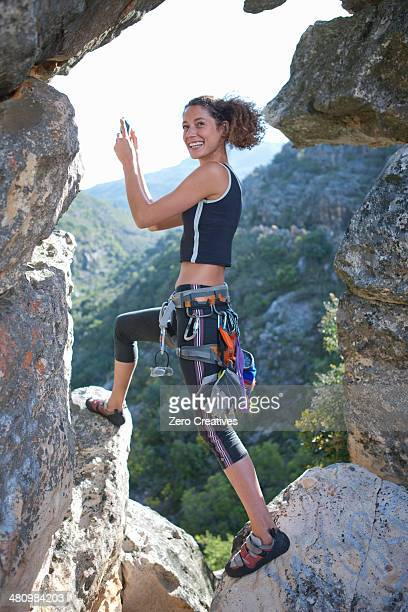 Young female rock climber taking selfie on smartphone