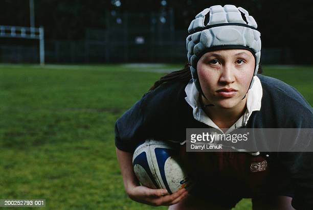 Young female rugby player crouching with ball, close-up, portrait