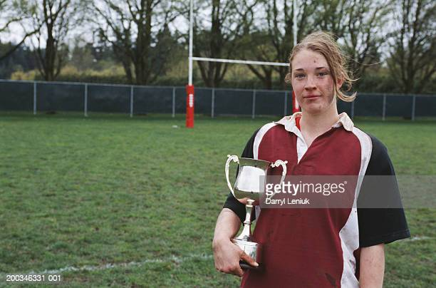 Young female rugby player with trophy, close-up, portrait