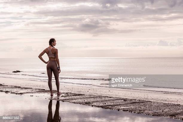 Young female runner at waters edge looking out to sea