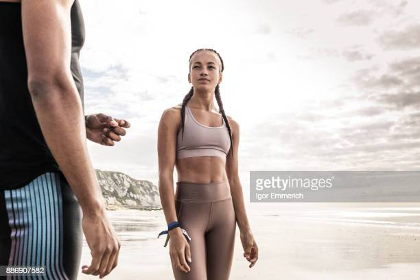 Young female runner gazing at young man on beach