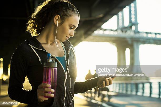 Young female runner holding water bottle, New York City, USA