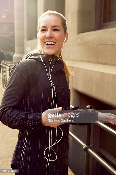 Young female runner listening to smartphone music on earphones