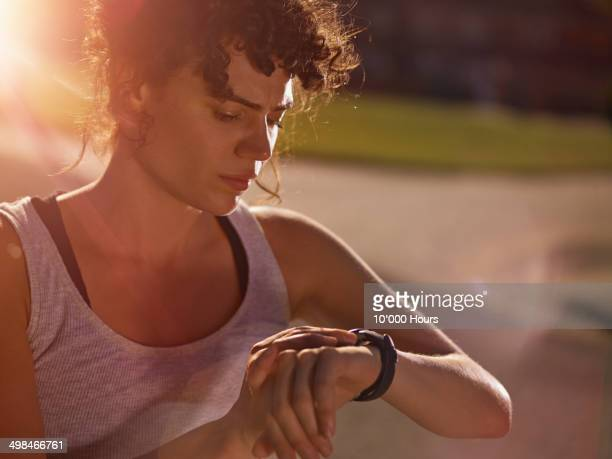 A young female runner, looking at her watch