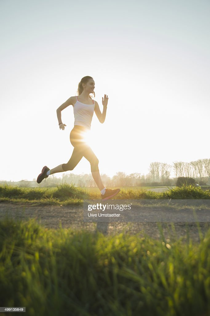 Young female runner on sunlit dirt track