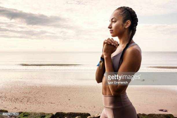 Young female runner preparing for run with hands together on beach