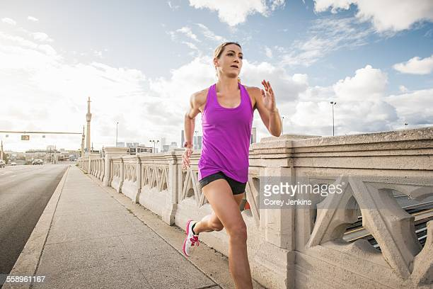 Young female runner running across bridge, Los Angeles, California, USA