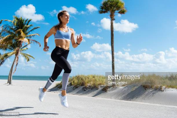 Young female runner running at beach