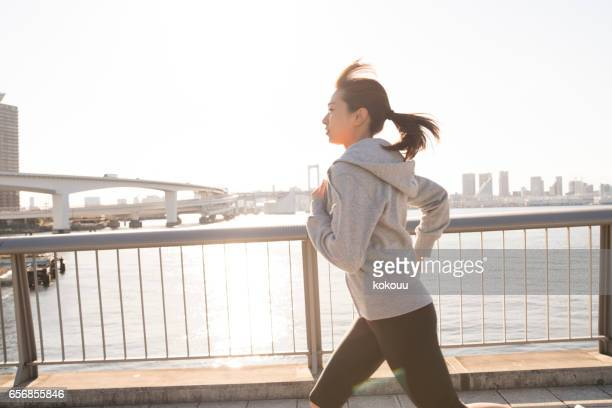 Young female runner running happily