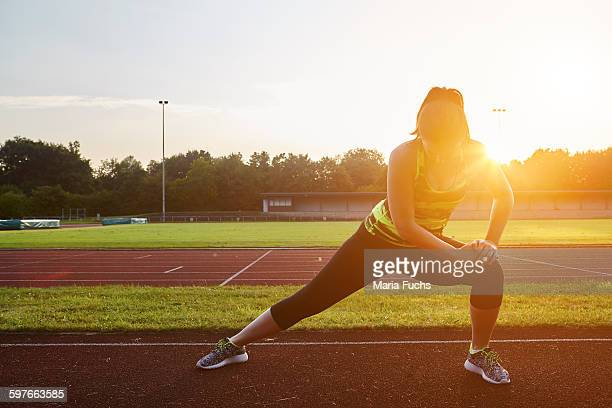 Young female runner stretching on sunlit race track