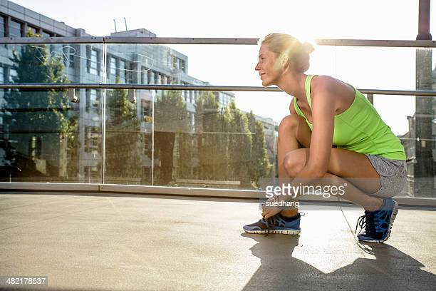 Young female runner tying shoelace on city footbridge
