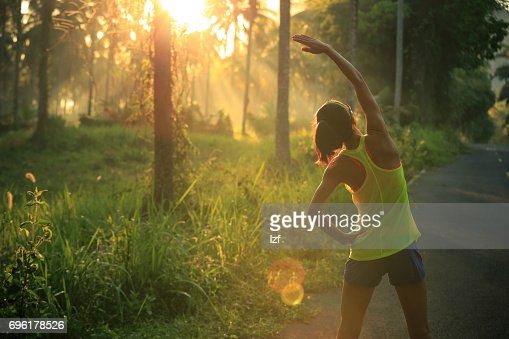 Young female runner warming up before running at morning forest trail : Stock Photo