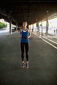 Young female runner watching from waterfront, New York City, USA