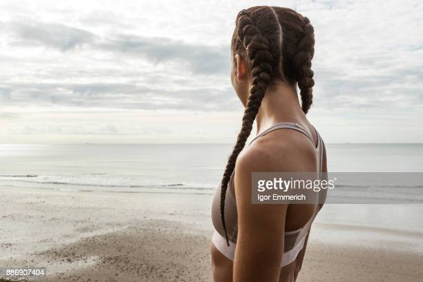 Young female runner with hair plaits looking out to sea from beach