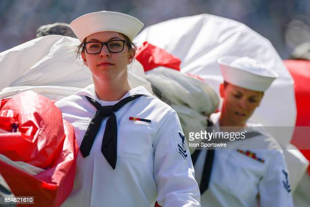 A young female sailor carries the flag off the field after the Star Spangled Banner is played during the NFL game between the New York Giants and the...