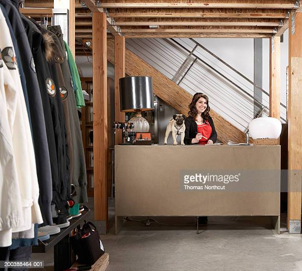 Young female sales clerk in retail store, pug on counter, portrait