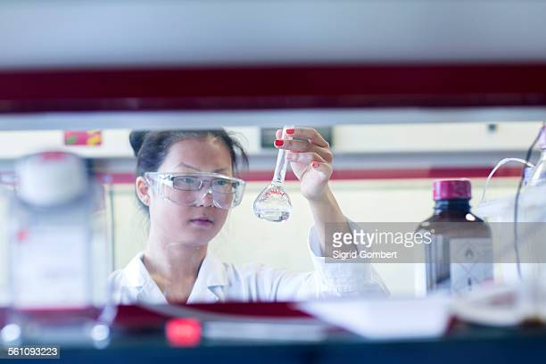 Young female scientist holding up volumetric flask in lab