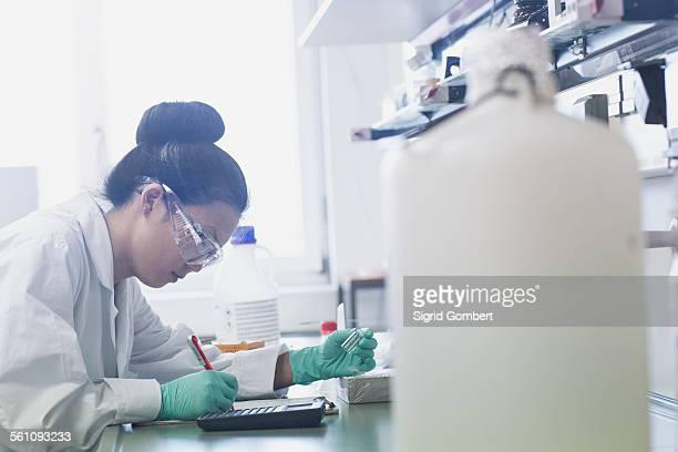 Young female scientist making research notes on lab workbench