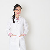 Portrait of young Asian female scientist with lab coat standing on plain background.